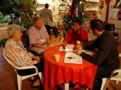 Messechefin im Gespräch mit Cuba Sí. Von rechts nach links: Harald Neuber (Journalist), Dalia Lopez (Messechefin), Rolf M. Hasse (AG der Bibliotheken in Niedersachsen), Messebesucherin