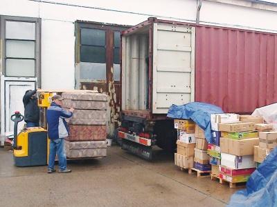 Die materiellen Spenden - sortiert und sicher verpackt - werden in den Container