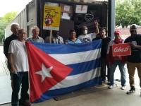 Die Helfer*innen stehen mit der kubanischen Flagge am vollbeladenen Container.